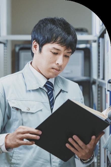 長野県の水と空気を守る中信アスナの社員が、本社資料室で設計書を読んでいる様子